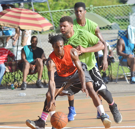 WARREN DILLAWAY / Star Beacon<br /> QUAZON LATHAM of Riding Dirty dribbles the ball  in front of Chick's Bar defenders Ace Jones (facing foreground) and Geovante Rose (back) on Saturday during the Westside Shootout at the West Avenue courts in Ashtabula.