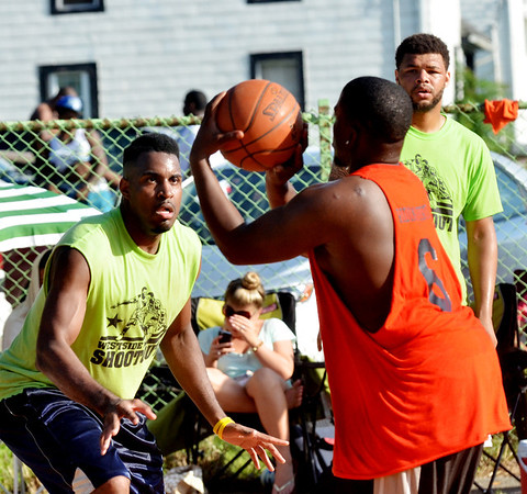 WARREN DILLAWAY / Star Beacon<br /> EMELIO PARKS of Chick's Bar (facing left) and teammate Ace Jones (facing right) defend Jeremy Moore of Riding Dirty on Saturday during the Westside Shootout at the West Avenue courts in Ashtabula.