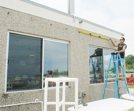 WARREN DILLAWAY / Star Becon<br /> JOHN MONDAY of Lake Front Properties prepares to build an awning for shade at the Breakwall Cafe in Conneaut Harbor.
