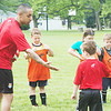 WARREN DILLAWAY / Star Beacon<br /> BAZ YAFAI (left), a coach at Challenger Soccer Camp, congratulates Eric Campbell, 6, on Friday at Conneaut Township Park. The soccer camp was held in conjunction with the CLYO youth soccer program.