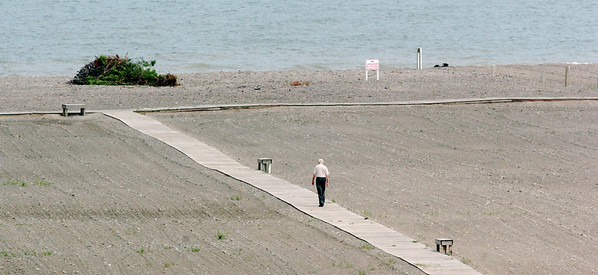 WARREN DILLAWAY / Star Beacon<br /> A LONE walker heads toward Lake Erie on the Conneaut Township Park boardwalk on Friday afternoon.
