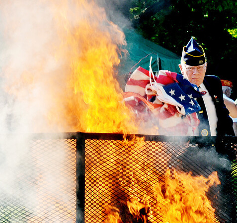 WARREN DILLAWAY / Star Beacon<br /> DUANE HATCH of Neal American Legion Post 743 in North Kingsville tosses flags into a fire during a flag retirement ceremony at Greenlawn Memory Gardens on Friday evening to celebrate Flag Day.