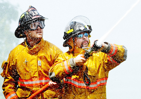 WARREN DILLAWAY / Star Beaco<br /> JOSH NEWTON (left) and Dan Cole of the Burghill Vernon Fire Department compete in the Firefighter Roundup at the Geneva-on-the-Lake Landing on Saturday afternoon.