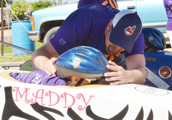 WARREN DILLAWAY / Star Beacon<br /> JOHN HOGAN helps prepare his daughter Maddy, both of Ashtabula, for a heat in the Soap Box Derby Saturday in Conneaut.