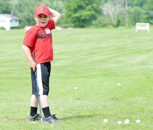 WARREN DILLAWAY / Star Beacon<br /> HUTER SPANGLER, 8, of Rome Township, looks to an instructor during the Hickory Grove Junior Golf Clinic on Tuesday in Jefferson Township.