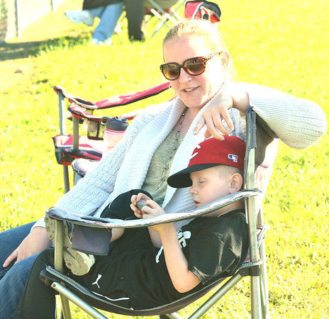 WARREN DILLAWAY / Star Beacon<br /> GAVIN FLETCHER, 5, huddles with his mother Jennifer Kessler, both of Conneaut, while playing on his mobile phone and watching his cousing play softball on Monday night at Skippon Park in Conneaut.