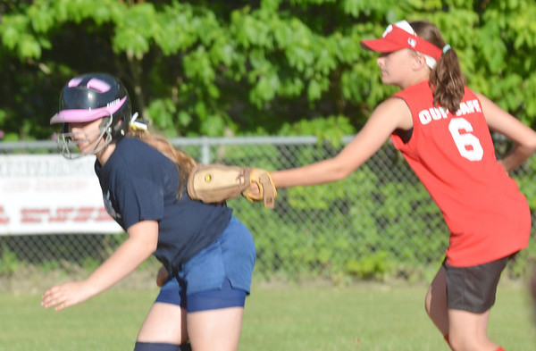 WARREN DILLAWAY / Star Beacon<br /> ASHLEY HALL of the Pymatuning Phillies Major League team tags Hannah Hunt of the Conneaut Blue team out during a run down on Monday evening at Skippon Park in Conneaut.