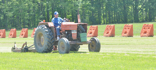 WARREN DILLAWAY / Star Beacon<br /> TRAFFIC BARRIERS seem to be frowning while Al Wetherbee mows the lawn at the Ashtabula County Fairgrounds in Jefferson.