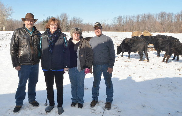 WARREN DILLAWAY / Star Beacon<br /> ORGANIZERS OF the Farm for Christ program gather at Ron Capitena's (far right) Kingsville Township farm. Traci Warren (second from left), president of the St. Vincent dePaul Society of Our Lady of Peace Parish in Ashtabula, and fellow society member Drew Thomas (far left) will work with  Diane Bradbury (third from left), director of the Country Neighbor Food Bank.  The organization hopes to raise money and animals for the needy of Ashtabula County .