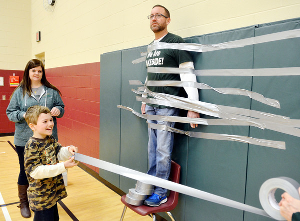 WARREN DILLAWAY / Star Beacon<br /> JEFF BAYLOR, a Superior Intermediate School, is taped to a  gymnasium wall on Friday in Ashtabula. Hayden Kelner, a fourth grader, was one of many students that helped complete the deed with the help of student council advisor Heather Gardner.