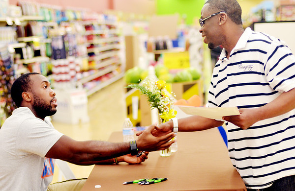 WARREN DILLAWAY / Star Beacon<br /> JAMES-MICHAEL JOHNSON, a Cleveland Browns linebacker, shakes hands with Mercedes Bankston Friday evneing at Giant Eagle in Saybrook Township during an autograph session to celebrate the store's recent renovation.