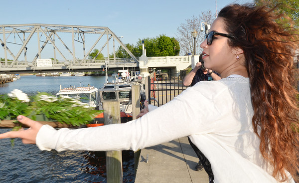 WARREN DILLAWAY / Star Beacon<br /> RAE ANN BENEDICT tosses a memorial wreath into the Ashtabula River on Saturday during the 64th Annual Blessing of the Fleet ceremony in Ashtabula Harbor.
