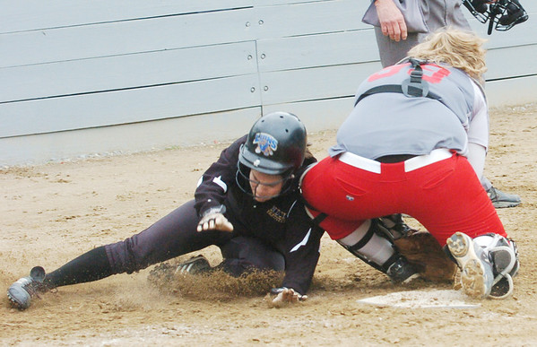 WARREN DILLAWAY / Star Beacon<br /> NICOLE GRIMMITT of Geneva (right) grabs for the ball as Camille Pollutro of Notre Dame Cathedral Latin arrives at home plate on Friday afternoon during the Division II district championship game at the Jefferson Area Girls softball complex.