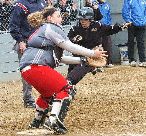 WARREN DILLAWAY / Star Beacon<br /> NICOLE GRIMMITT of Geneva (left) waits for the ball as Camille Pollutro of Notre Dame Cathedral Latin arrives at home plate on Friday afternoon during the Division II district championship game at the Jefferson Area Girls softball complex.