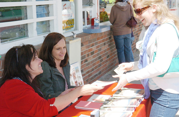 """WARREN DILLAWAY / Star Beacon<br /> WENDY HOILE, author of """"A History of Ohio's First Summer Resort"""" hands a book to Julie Hallas of Columbus during a book singing on Saturday in front of Eddie's Grill at Geneva-on-the-Lake."""