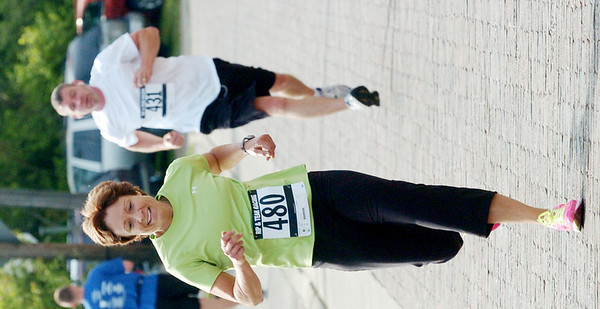 WARREN DILLAWAY / Star Beacon<br /> JEANNINE BARTLETT (480) of Ashtabula and Mike Miklacic of Ashtabula race to the finish line of the Memorial Day Lift Bridge 5K Monday in Ashtabula.