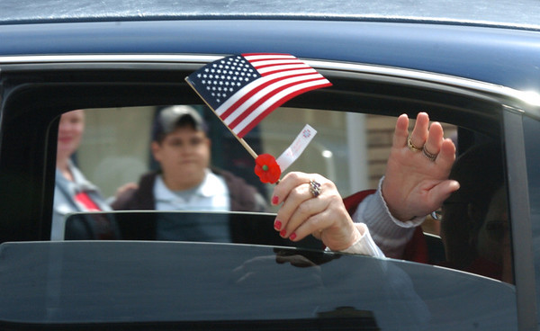 WARREN DILLAWAY / Star Beacon<br /> A SMALL American flag is waved from a limousine that transported veterans who were unable to walk in the Ashtabula Memorial Day parade on Monday.