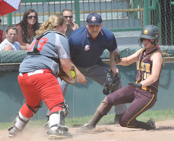 WARREN DILLAWAY / Star Beacon<br /> NICOLE GRIMMETT (left) of Geneva prepares to tag out Taylor Stimson of Walsh Jesuit during a Division II regional semi-final game at Firestone Park in Akron on Thursday afternoon. Umpire Anthony Montana called Stimson out at the plate.