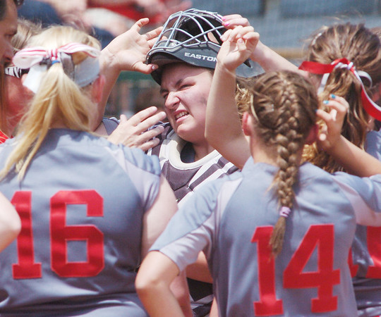 WARREN DILLAWAY / Star Beacon<br /> NICOLE GRIMMETT (wiith mask) gathers with her Geneva teammates on Thursday during a Division II regional semi-final game at Firestone Park in Akron.