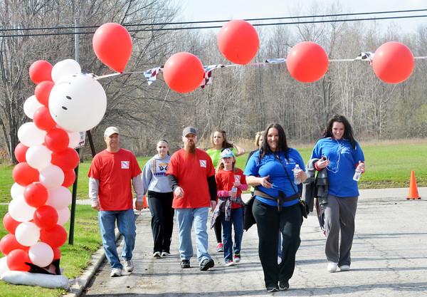 WARREN DILLAWAY / Star Beacon<br /> AMY BARKER of Ashtabula leads a group of walkers across the finish line of the Ashtabula County Heart Walk on Saturday at Kent State University-Ashtabula Campus.
