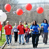 WARREN DILLAWAY / Star Beacon<br /> AMY BARKER of Ashtabula leads a group of walkers across the finish line of the Ashtabula County Heart Walk on Saturday at Kent State University-Ashtabula Campus.