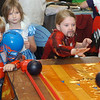 WARREN DILLAWAY / Star Beacon<br /> BRYONNA FORBES, 7, plays childrens games Saturday during the N.E. Geek Expo at the Ashtabula County Fairgrouds with Riley Messent, 7, (back left) and Keegan Messent, 4, (front left), all of Ashtabula, watching the game.