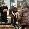 WARREN DILLAWAY / Star Beacon<br /> GABBY SHERBEYN (center) channels her inner Zombie to greet trick or treaters with Joyce Kren (left) on 45th Street in Ashtabula Saturday afternoon.
