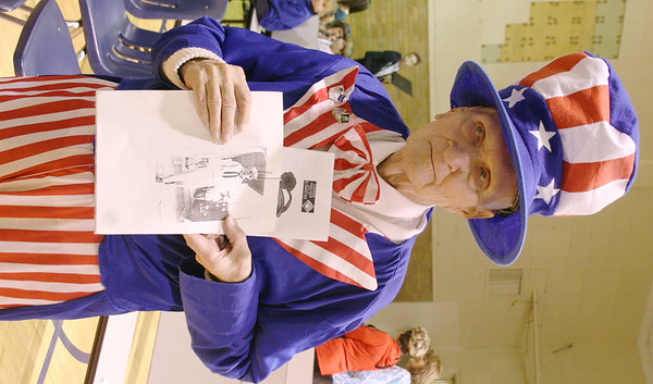 MARGIE NETZEL / Star Beacon<br /> NAVY VETERAN Frank Starkey shows off a picture of himself as a young serviceman in Honolulu in 1944. Starkey, 87, was honored at the St. John School Veteran's Day program Monday.