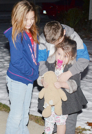 WARREN DILLAWAY / Star Beacon<br /> ETHAN BALES, 9, helps his sister Emerson, 4, while Kennedy  Bales (left) looks on early Thursday morning during a family fire drill on East Main Street in Geneva.