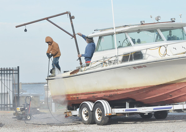 WARREN DILLAWAY / Star Beacon<br /> GARRETT GREENE, 11, (left) and Mark Baker, both of Conneaut, prepare a boat for winter at Conneaut Harbor Friday afternoon.