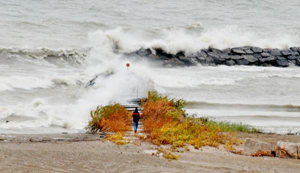 WARREN DILLAWAY / Star Beacon<br /> A LONE man walks toward the Conneaut Breakwall as waves crash the shoreline on Friday afternoon  at Conneaut Township Park.