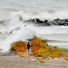 WARREN DILLAWAY / Star Beacon<br /> A LONE man walks toward the Conneaut Breakwall as waves crash the shoreline on Friday afternoon  at Conneaut Township Park.