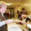 WARREN DILLAWAY / Star Beacon<br /> ALYCIA COLON of Ashtabula serves Richard Lewis of Cleveland during a Thanksgiving Dinner at G.O. Ministries Thursday morning in Ashtabula.
