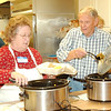 WARREN DILLAWAY / Star Beacon<br /> SUE DRAKE and Carl Louden serve Thanksgiving Dinners at the Geneva Community Center Thursday.