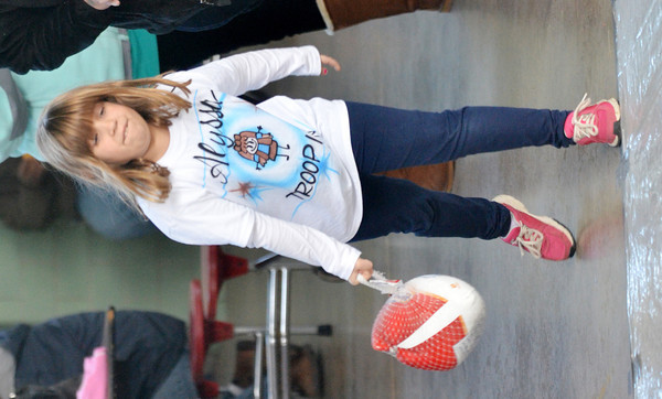 WARREN DILLAWAY / Star Beacon<br /> ALYSSA PETTURA, 7, of Howland, prepares to release her frozen turkey during turkey bowling on Saturday at Lighthouse Harvest Foundation in Ashtabula Township. The event was sponsored by girl scout troop 80103.