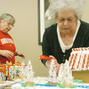 WARREN DILLAWAY / Star Beacon<br /> LINDA JAMESON of Akron (right) works on a gingerbread house as Frances Hoover of Crestview takes a break during the Gingerbread Challenge at the Lodge and Convention Center at Geneva-on-the-Lake Saturday.