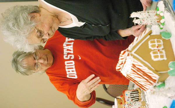 WARREN DILLAWAY / Star Beacon<br /> LINDA JAMESON of Akron (right) works on a gingerbread house with Frances Hoover of Crestview takes a break during the Gingerbread Challenge at the Lodge and Convention Center at Geneva-on-the-Lake Saturday.