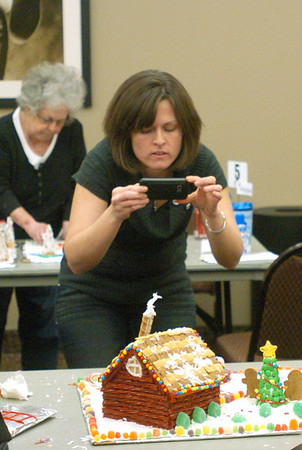 WARREN DILLAWAY / Star Beacon<br /> LORI MIKULKA of Twinsburg takes a picture of a gingerbread house during the Gingerbread Challange at the Lodge and Convention Center at Geneva-on-the-Lake Saturday.