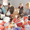 WARREN DILLAWAY / Star Beacon<br /> MEGAN STUPER (left) and Renee Schroer (second from right) prepare turkeys for people to take home for Thanksgiving Dinner on Saturday at the Salvation Army on Lake Avenue in Ashtabula. Clyde Huston (holding white bag) and Coral Huston, both of Ashtabula, (with box and bag)  chat before leaving with their food on Monday morning.