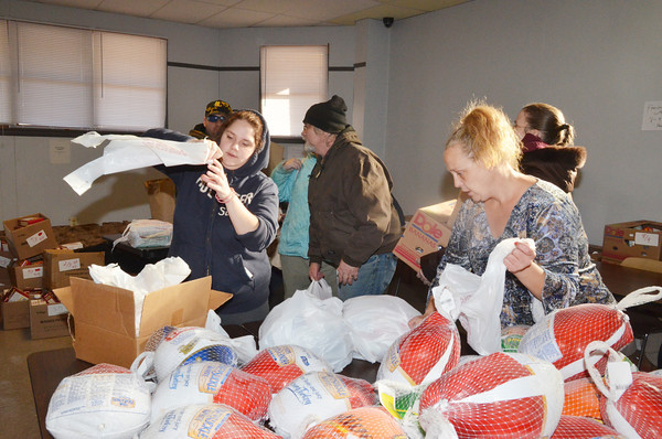 WARREN DILLAWAY / Star Beacon<br /> MEGAN STUPER (left) and Renee Schroer (right) prepare turkeys for people to take home for Thanksgiving Dinner on Saturday at the Salvation Army on Lake Avenue in Ashtabula. Clyde Huston (center) and Coral Huston, both of Ashtabula, (partially hidden right behind) leave with their food on Monday morning.