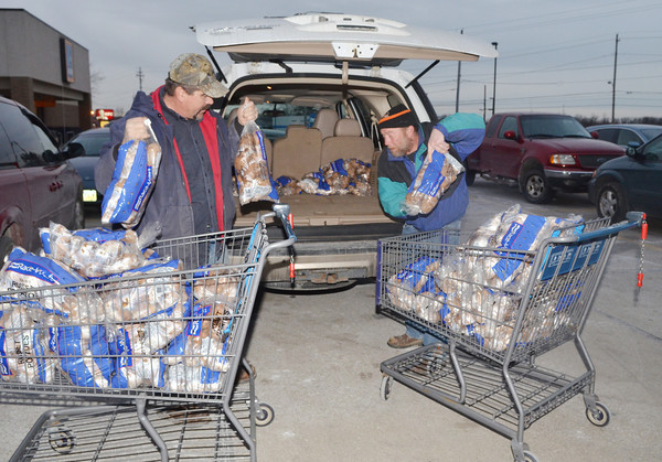 WARREN DILLAWAY / Star Beacon<br /> MATT BREWSTER (left) and Charles Crim, load food during   a shopping trip for the Harassmeents Food Drive on Monday evening.