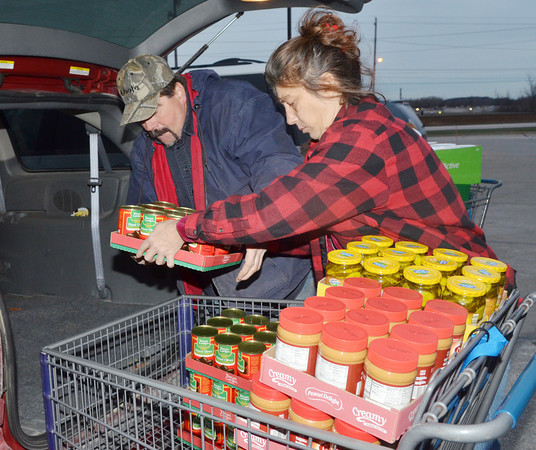 WARREN DILLAWAY / Star Beacon<br /> MATT BREWSTER (left) and Kim Wick, both of Jefferson,  load food during a shopping trip for the Harassments Food Drive on Monday evening in Ashtabula.