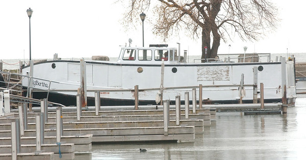 WARREN DILLAWAY / Star Beacon<br /> A DUCK swims near empty docks near the only boat still in the water in Conneaut Harbor.