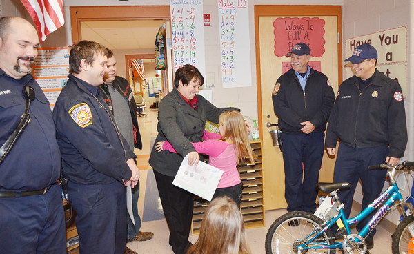 WARREN DILLAWAY / Star Beacon<br /> MEMBERS OF the Conneaut Fire Department (from left) Terry Burr and Anthony Nelson watch as Kristina Ingram hugs her daughter Adia Ingram, a first grader at Lakeshore Elementary School after she won a bike in a Conneaut Fire Department Safety Poster Contest. Jason Ingram, third from left, watches his daughter with Captain John Chapin (second from right) and Chad Carter look on.