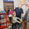 WARREN DILLAWAY / Star Beacon<br /> NATALIE WOOD, a second grader at Lakeshore Primary School, reacts after receiving a bike from members of the Conneaut Fire Department. She was one of two students that won bicycles after winning a poster safety contest sponsored by the Conneaut Fire Department. Wood sits on her bike for the first time as school principal Jim Kennedy (right) and her mother Stephanie Wood (in doorway)  react after Conneaut firefighters Anthony Nelson (left) and Terry Burr (between Kennedy and Wood) presented the bicycle.