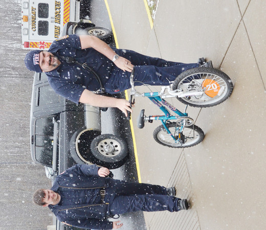 WARREN DILLAWAY / Star Beacon<br /> TERRY BURR (right) and Anthony Nelson, both Conneaut firefighters, deliver a bicycle to Lakeshore Primary School on Tuesday afternoon. Two students won bikes in a Conneaut Fire Department safety poster contest.