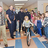 WARREN DILLAWAY / Star Beacon<br /> NATALIE WOOD, a second grader at Lakeshore Primary School, gets to ride her bike down the hall after members of the Conneaut Fire Department presented it to her. She was one of two students that won bicycles after winning a poster safety contest sponsored by the Conneaut Fire Department.