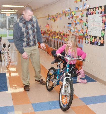 WARREN DILLAWAY / Star Beacon<br /> ADIA INGRAM, a first grader at Lakeshore Primary School in Conneaut, gets to try out her new bicycle in the school's hallway under the watchful eye of principal Jim Kennedy on Tuesday afternoon. She was one of two students who won a bike from the Conneaut Fire Department Safety Poster Contest.