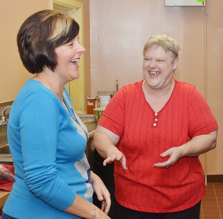 WARREN DILLAWAY / Star Beacon<br /> ROSE BRAMER (right), coordinator of a Thanksgiving dinner at the Geneva Community Center talks with volunteer Becky Osborne on Thursday afternoon.