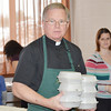 WARREN DILLAWAY / Star Beacon<br /> FATHER PHILIP MILLER helps serve meals during a  Thanksgiving dinner at Corpus Christi Parish in Conneaut Thursday afternoon.